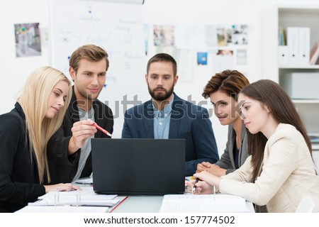 Serious group of diverse professional young business people in a meeting sitting at a table consulting information on a laptop computer - stock photo