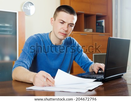 serious guy staring financial documents at table in home interior