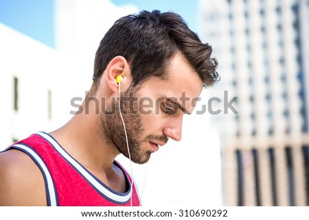 Serious handsome athlete listening to music on a sunny day - stock photo