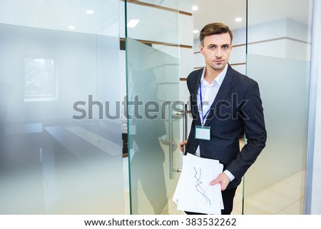 Serious handsome business man holding financial report and entering the meeting room - stock photo