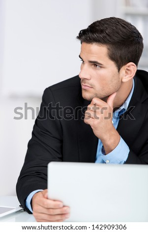 Serious handsome caucasian businessman sitting at the desk with a laptop computer in the office, with a pensive expression - stock photo