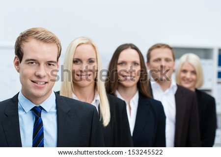 Serious handsome young business manager with his successful team of diverse business people lined up behind him