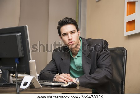 Serious handsome young businessman sitting at his desk in the office looking at camera