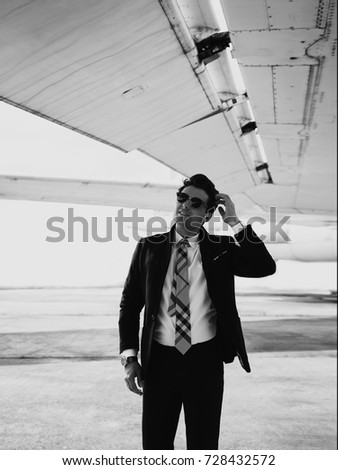Serious handsome young man in the west and suit walk near plane on the airfield