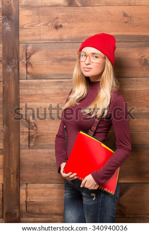 Serious hipster businesswoman posing with red folder isolated on wooden background. Beautiful lady with blond hair posing in casual clothes. - stock photo