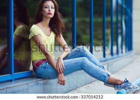 Serious hipster girl in blue jeans in the summer city. Modern youth lifestyle concept. Outdoor shot