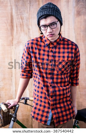 Serious hipster holding a bike on wooden background