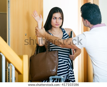 Serious husband trying to stop girl leaving him at doorway - stock photo