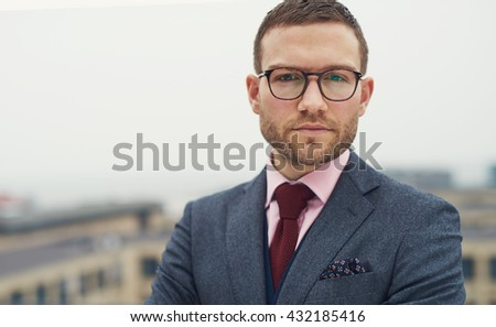 Serious intense young businessman with glasses standing outdoors on an open-air balcony staring at the camera, head and shoulders with copy space - stock photo