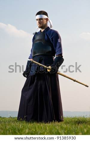 Serious kendo fighter with bokken standing - stock photo