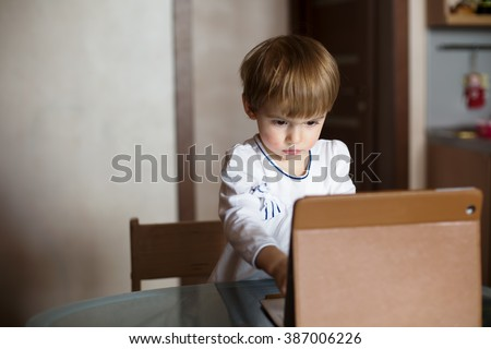 Serious Kid Little girl using tablet pc at home. Technology childhood, learning and communication with internet - stock photo