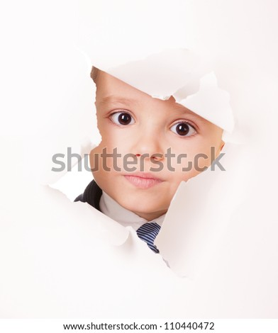 Serious kid looks through a hole in white paper