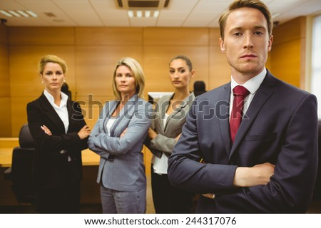 Serious lawyer standing with arms crossed in the court room - stock photo