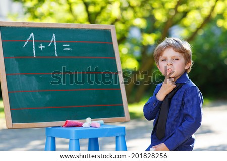 Serious little boy at blackboard practicing mathematics, outdoor school or nursery. Back to school concept