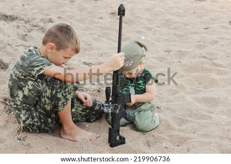 Serious little boy in military uniform plays in the war on the beach with arms - stock photo