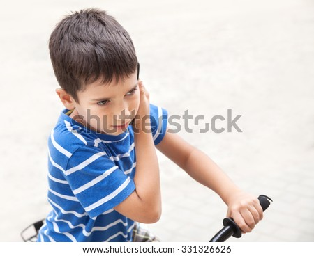 Serious little boy talking on the phone with his parents on light background with copy-space. Shallow DOF - stock photo