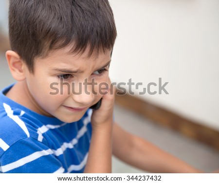 Serious little boy talking on the phone with his parents on light background with copy-space. Shallow DOF. - stock photo