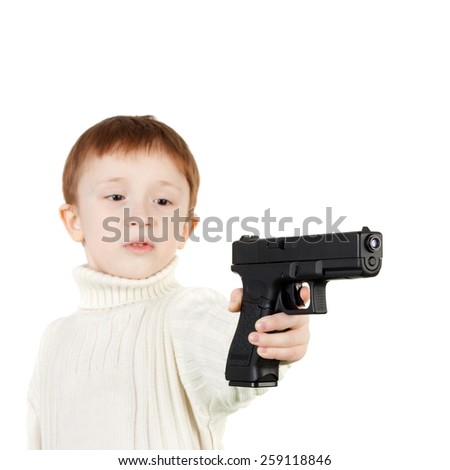 serious little boy with the big black pistol, focus on the pistol - stock photo
