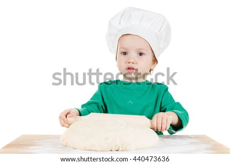 Serious little cook boy kneading the dough for the pizza, isolated on white background.  Half-length portrait of the table in studio - stock photo
