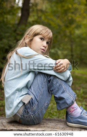 serious little girl nine years old sitting on bench in park - stock photo