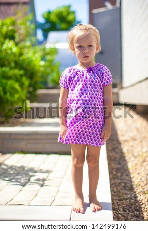 Serious little girl stands in front of her home