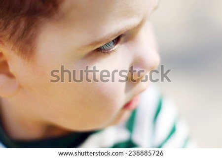 Serious little handsome boy looks at camera in park. Shallow dof - stock photo