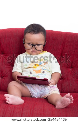 serious little sweet child enjoying modern generation technologies playing indoors using tablet pc with touchscreen - stock photo