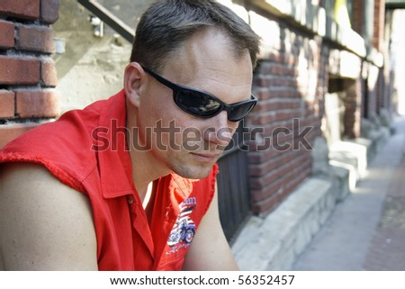 Serious male biker deep in thought while sitting on curb of old street. - stock photo