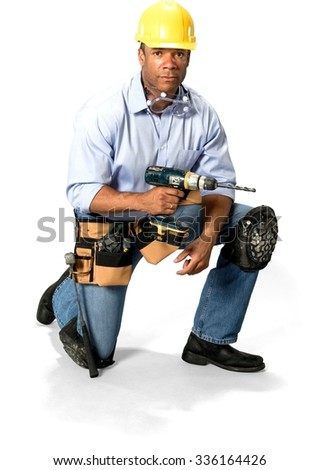 Serious Male Construction Worker with short black hair in uniform using drill - Isolated - stock photo