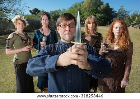 Serious male pagan priest with group and dagger outdoors - stock photo