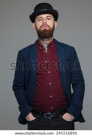 Serious male with tattooes in blue costume in hat - stock photo