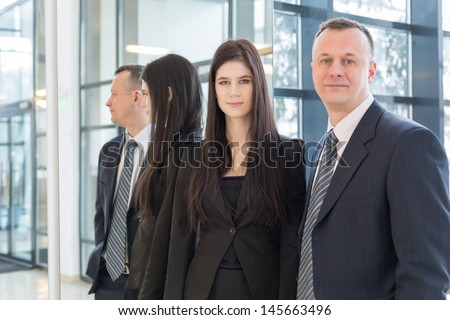 Serious man and woman in business suits stand near the mirror, focus on a girl