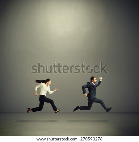 serious man and woman in formal wear running fast in grey empty room - stock photo