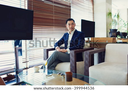 Serious man entrepreneur is waiting for important meeting with foreign partners for the signing of a cooperation agreement next year, while is sitting near screens with copy space for your content - stock photo