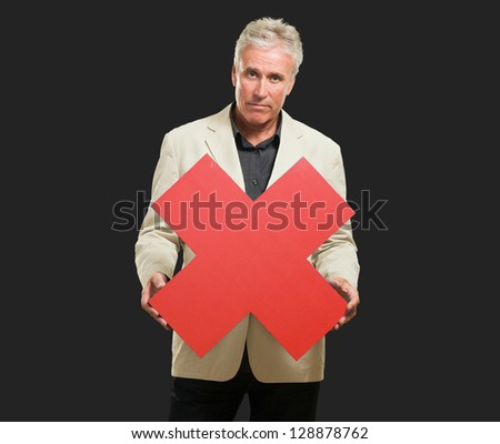 Serious Man Holding Red Cross Sign against a black background - stock photo
