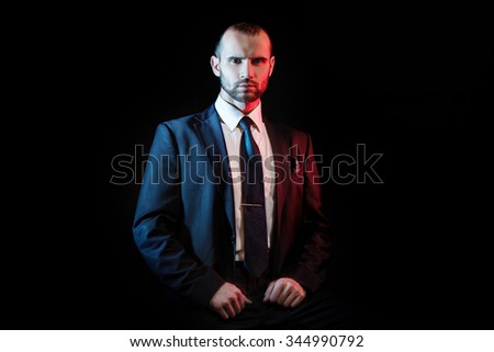 serious man in a business suit, dark background, backlight blue and red tones - stock photo