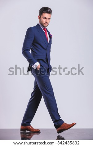 serious man in business suit pose while walking with hands in pockets - stock photo