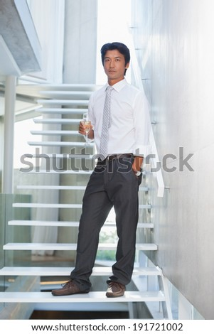 Serious man looking at camera holding champagne flute on the stairs