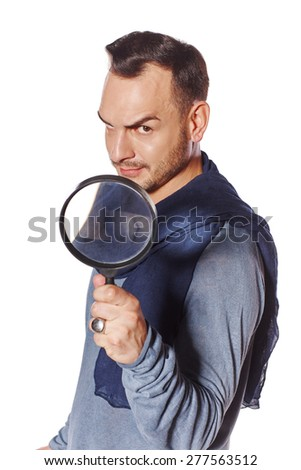 Serious man looking through magnifying glass  with a speculative look on his face looking at the camera, over white background. Search concept.