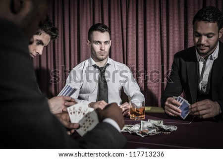 Serious man looking up from high stakes poker game in casino - stock photo