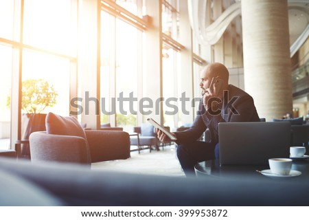 Serious man managing director of big prosperous company is holding touch pad and calling to manager to hear the explanation of why the client left a negative review about service on official website - stock photo