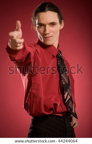 Serious man pointing on red background - stock photo