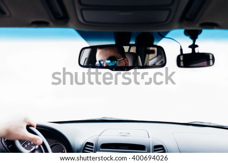 Serious man sitting at back seat of the car and have phone call. Closeup of rear view mirror.