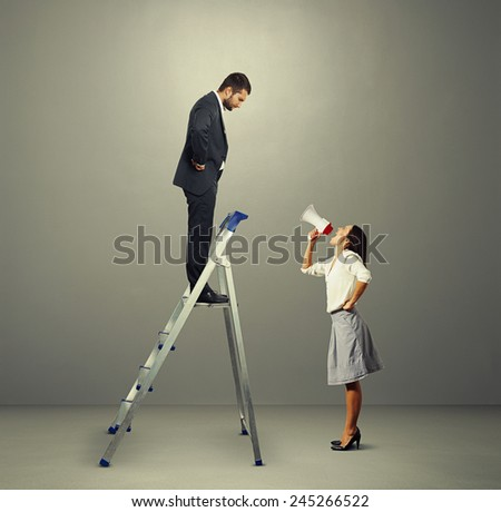 serious man standing on stepladder and looking screaming woman with megaphone. photo in grey empty room - stock photo