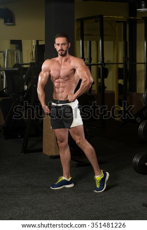 Serious Man Standing Strong In The Gym And Flexing Muscles - stock photo