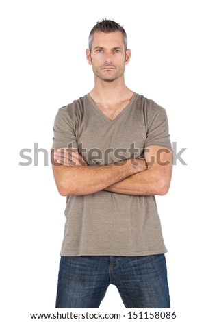 Serious man with arms crossed looking at the camera - stock photo