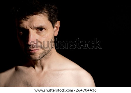 Serious Man With Half Face In Shadow - stock photo