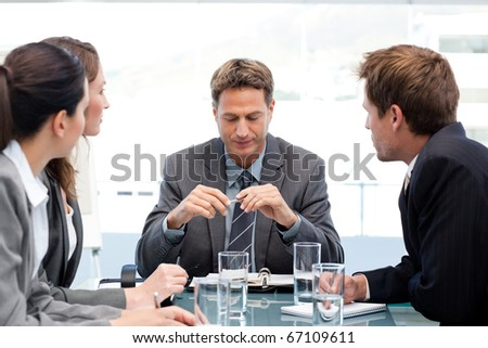 Serious manager at a table with his team during a meeting at the office - stock photo
