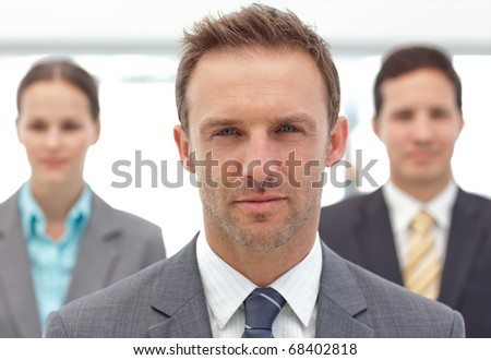 Serious manager posing in front of his two employees in the office - stock photo