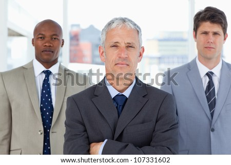 Serious manager standing in front of his two young executives - stock photo